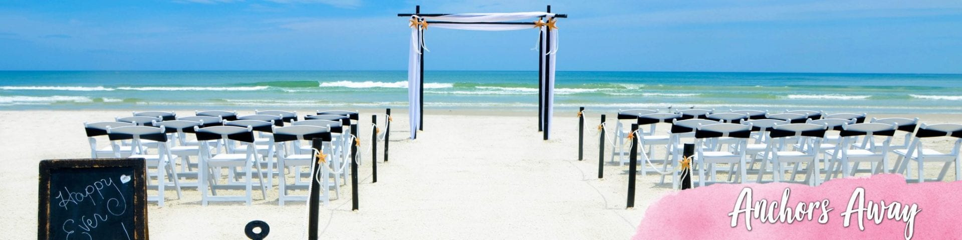 Black and white beach wedding arch and chairs and anchors