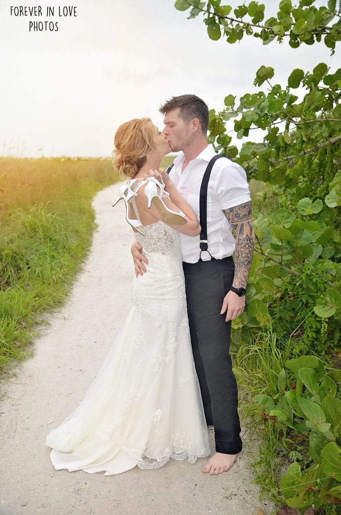 Wedding Couple kisses on sand walkway to Ponce Inlet Beach