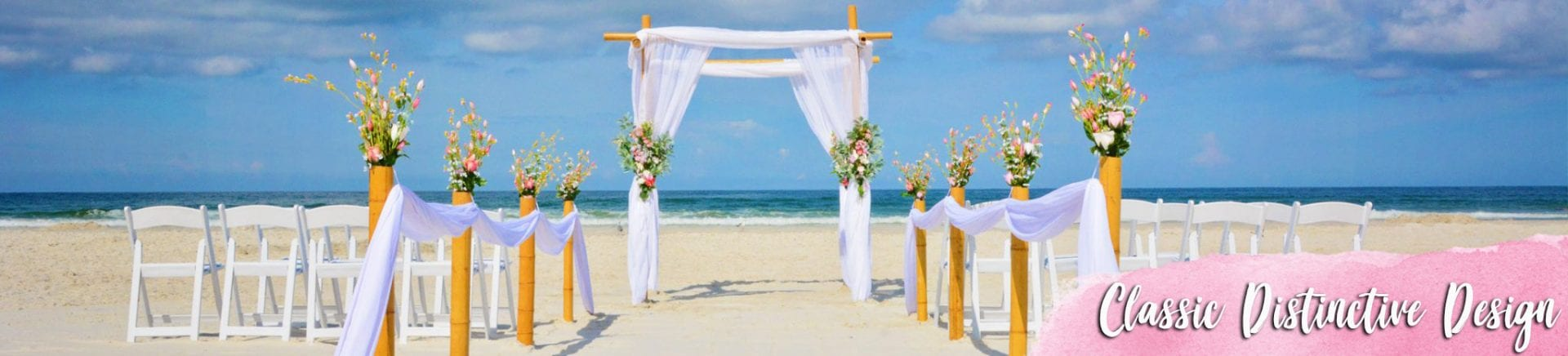 Classic design wedding arch with white draping and flowers on beach in Florida