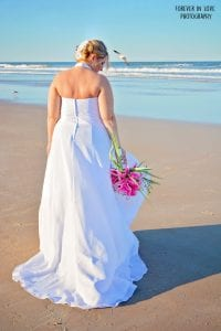 A bride poses during one of our Daytona Beach Weddings with her bouquet.