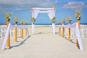 Classic White draping with sprays of pastel flowers are a feature in one of the beach Wedding Packages in Florida.