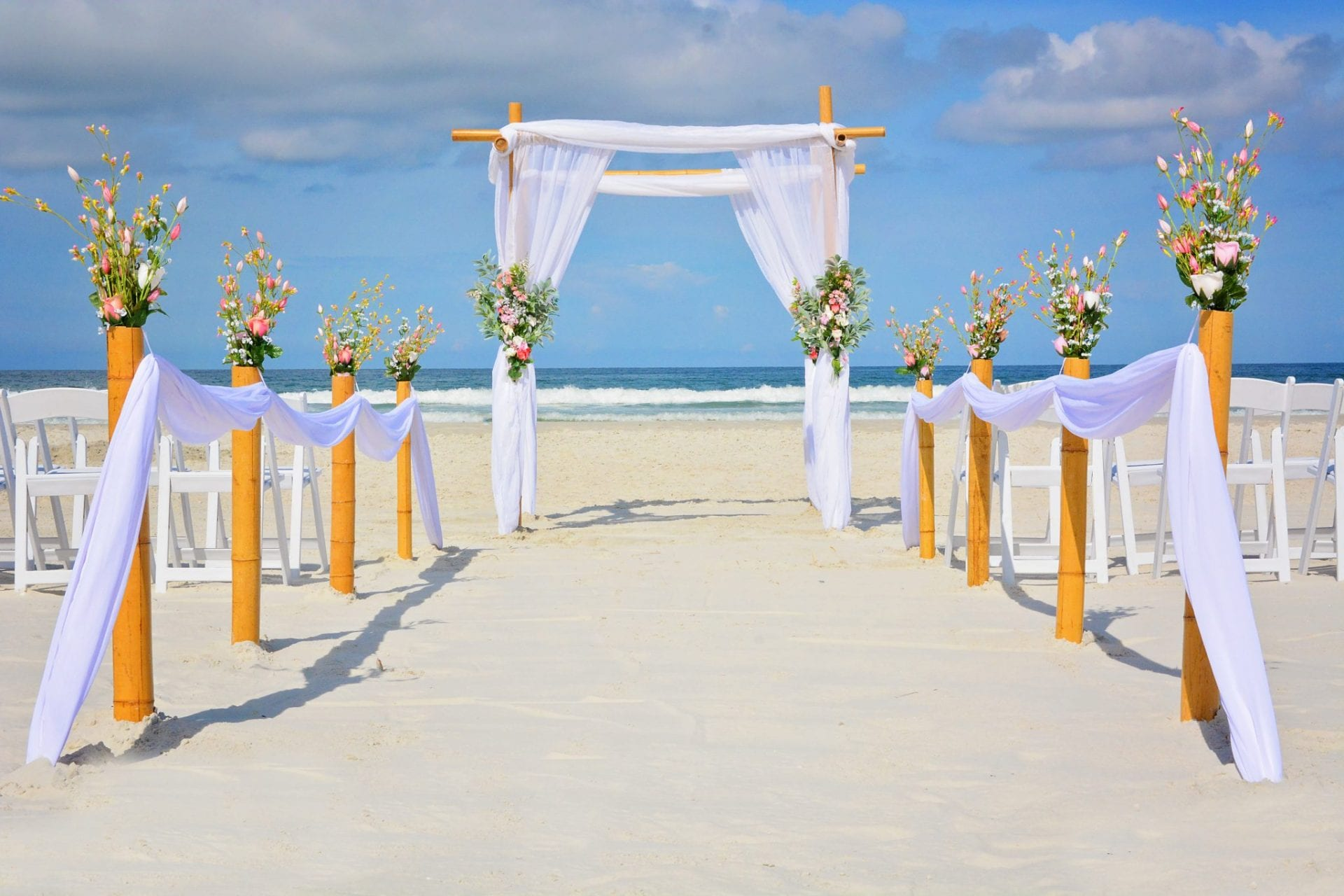 Floral draped bamboo wedding arch on the Florida beach