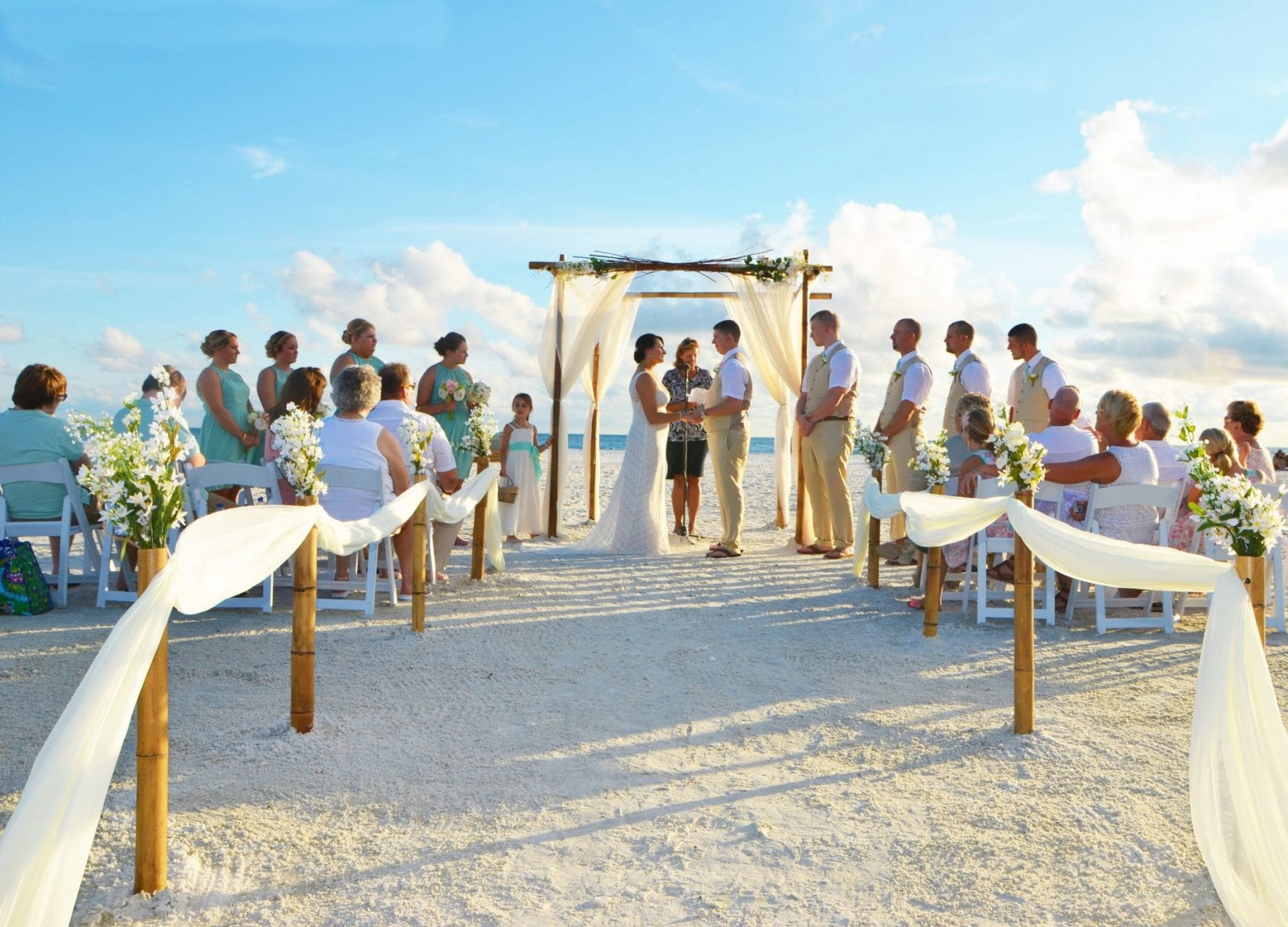 Draped floral wedding arch with couple saying vows on the beach