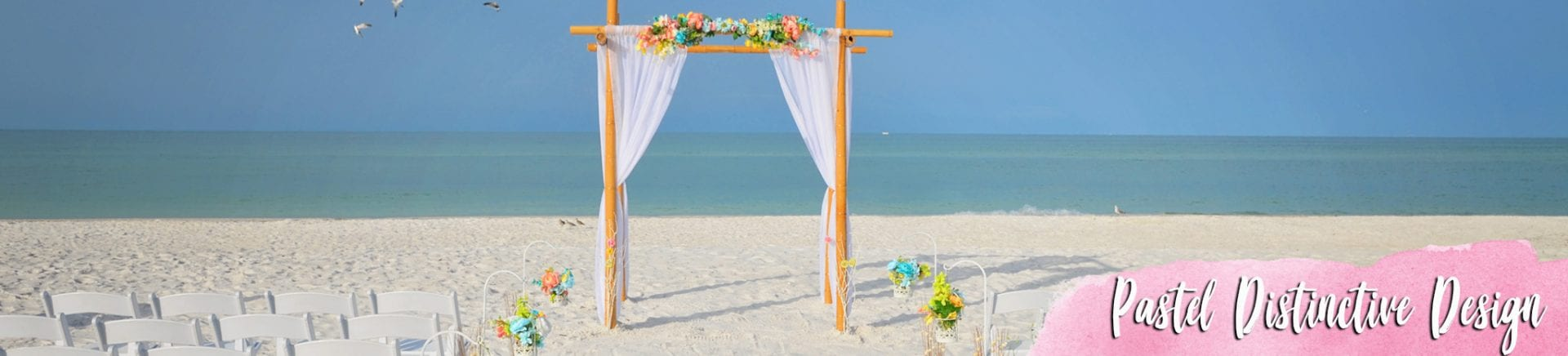 Pastel tropical flowers on wedding arch at beach