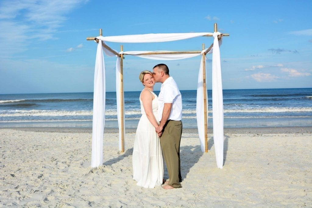 Daytona Beach Wedding couple with bamboo canopy eloping kissing on sand.