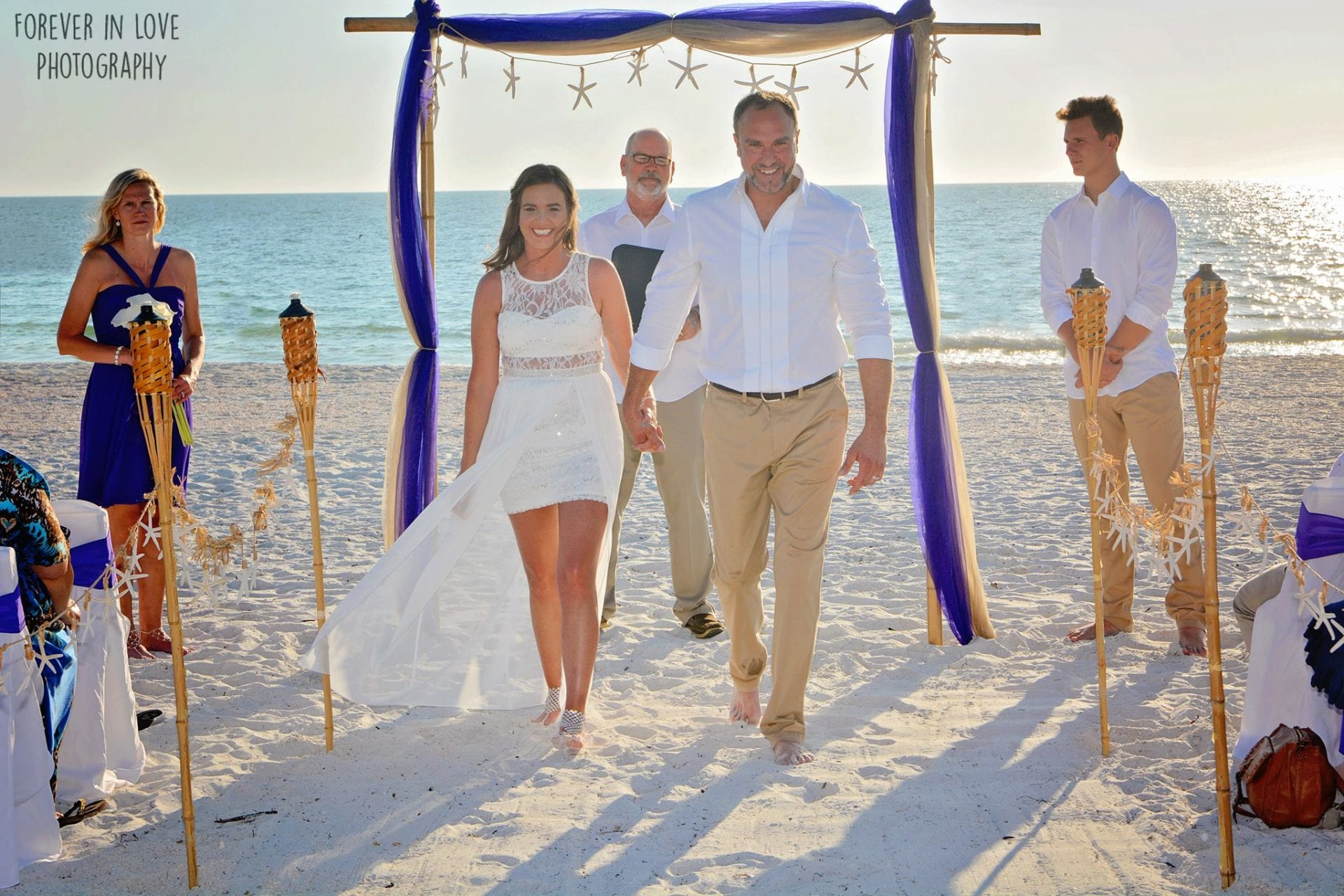 Couple holding hands at beach wedding ceremony