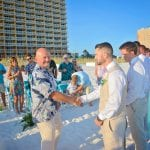 The brides dad welcomes his new son during one of our Destin, Florida beach weddings.
