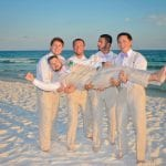 A groom is held up by his groosman during our Destin, Florida beach weddings.