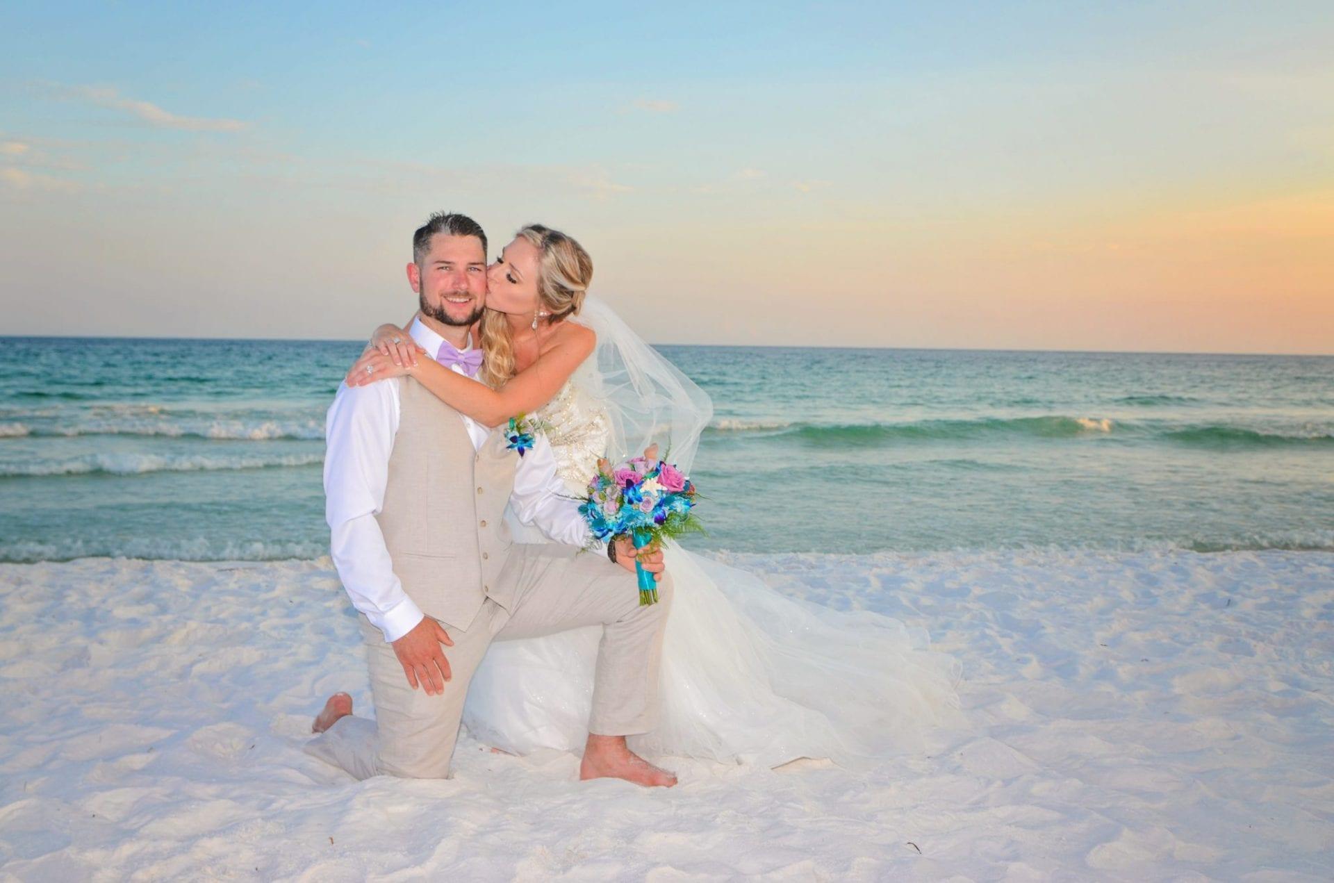 Bride kissing kneeling groom on beach