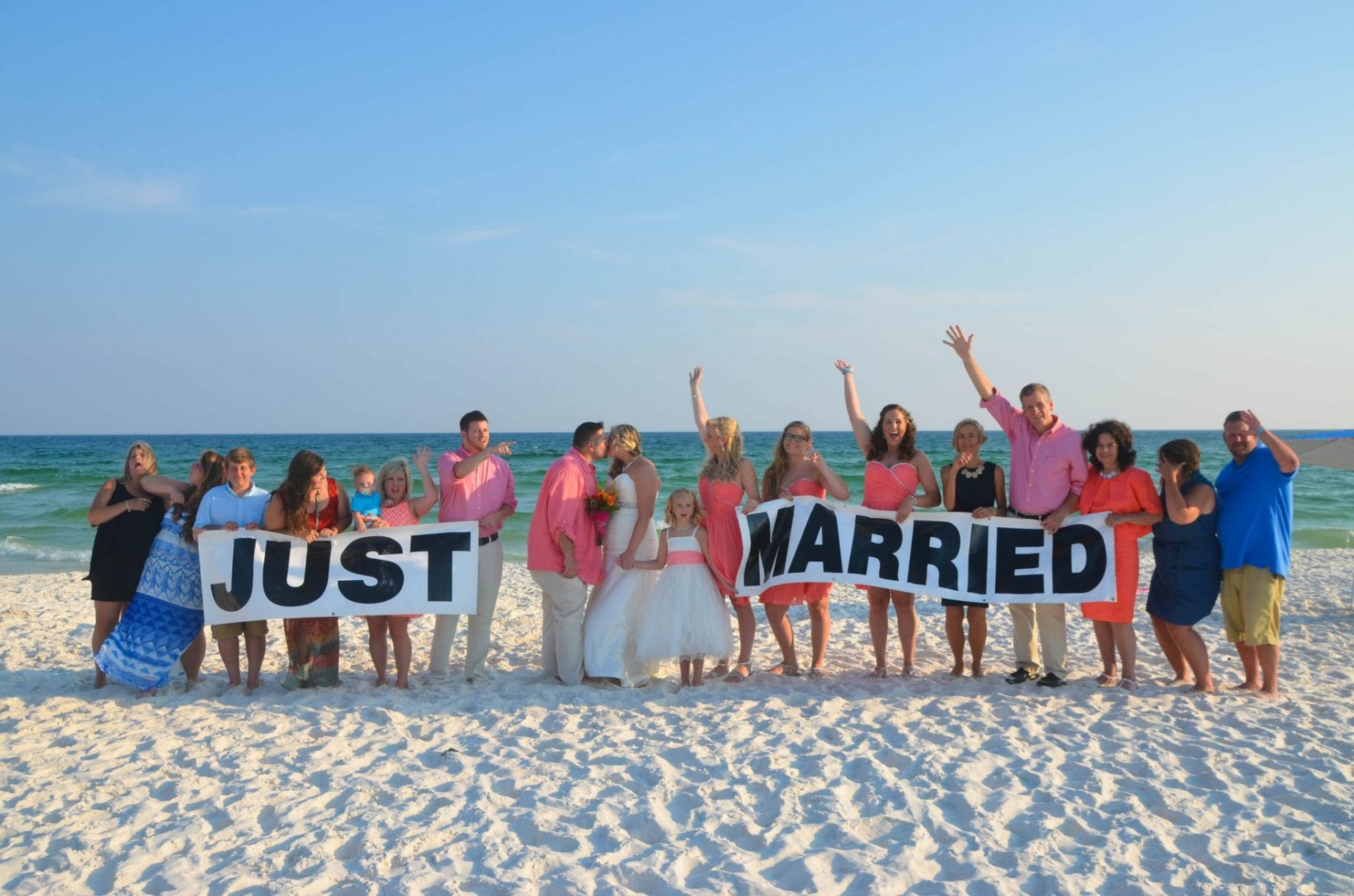 Beach wedding party holding up just married sign on Fort Walton Beach, FL