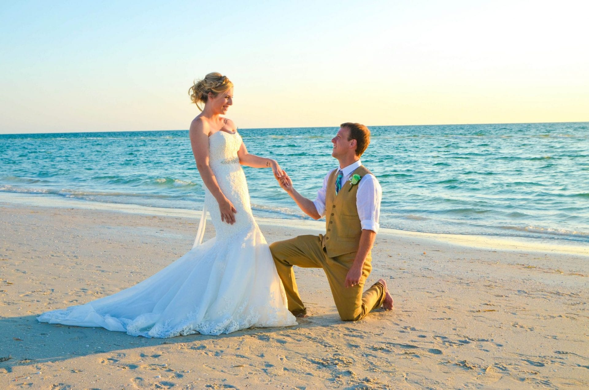 Wedding couple at Indian Rocks beach with groom kneeling