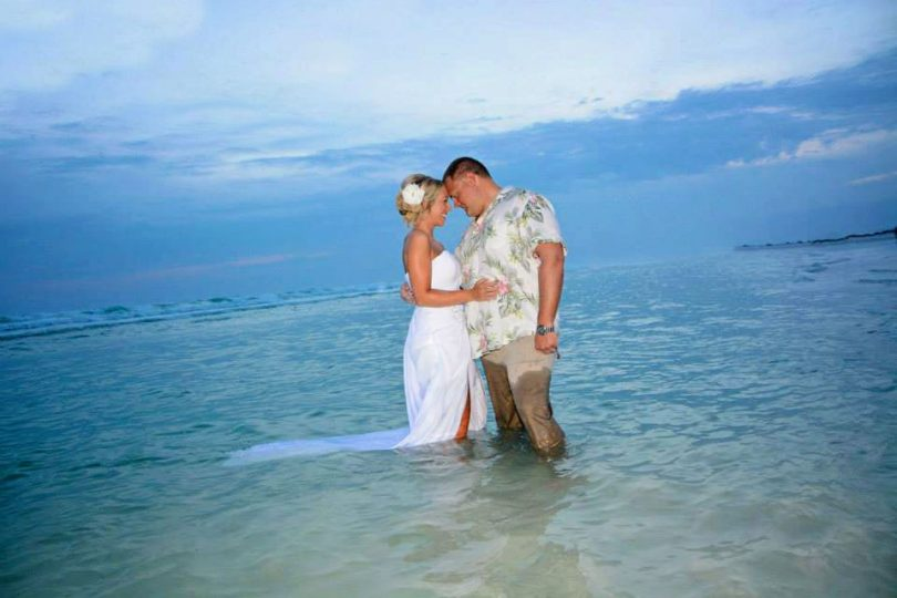 A bride and groom in the Gulf water during one of our Pensacola beach weddings.