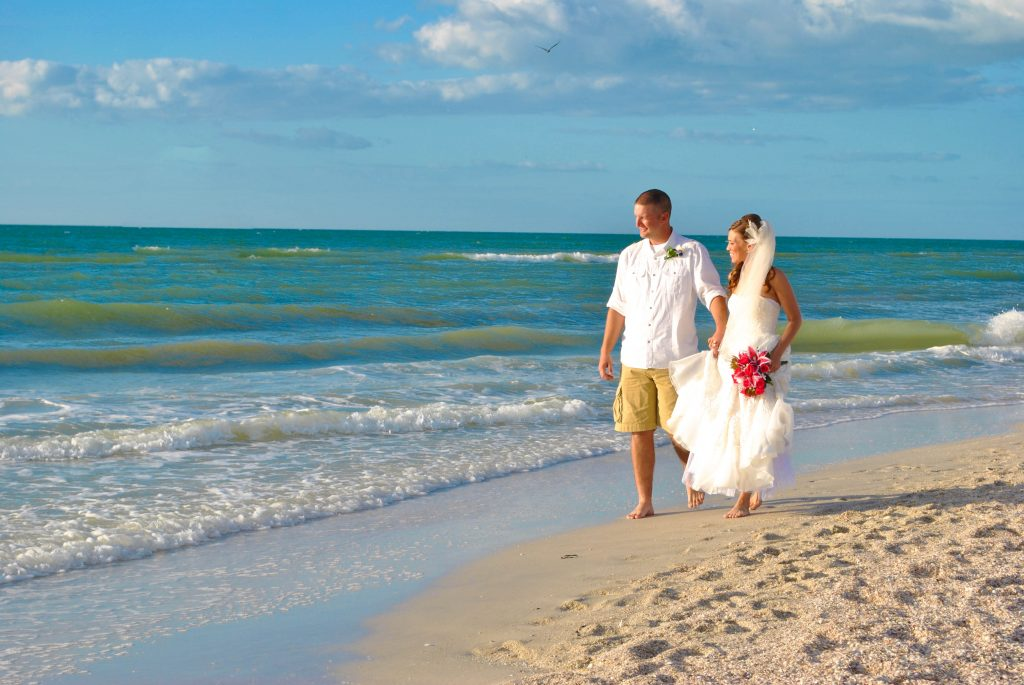 A bride and groom enjoy a walk on the beach during their Redington Beach