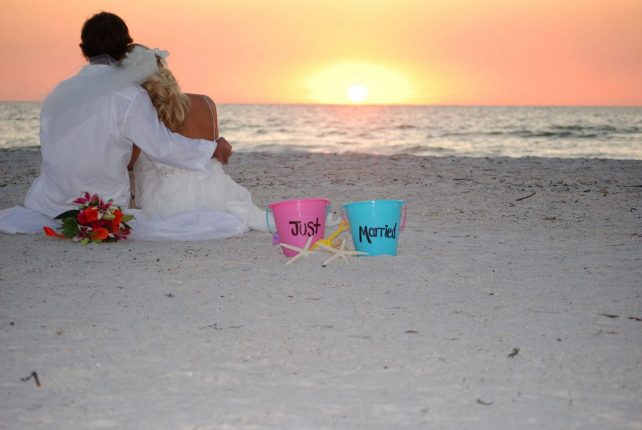 St. Pete Beach Wedding couple sitting on sand during sunset in Florida.