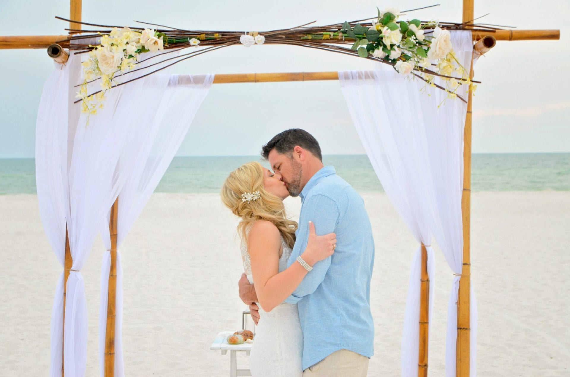 Couple kissing under floral beach arch