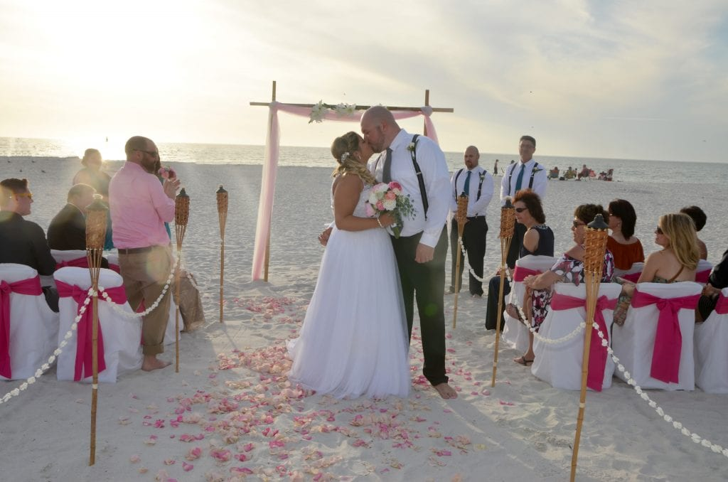 Couple kissing at Indian Rocks Beach Wedding with canopy, chairs, and officiant.