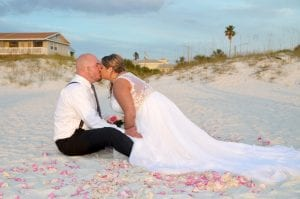 A bride and groom kiss in front of the dunes of their Clearwater Beach Weddings.