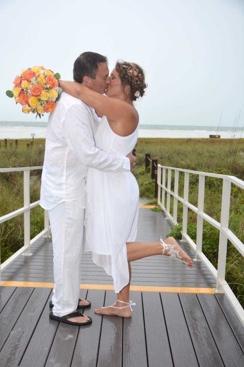 Wedding couple kissing on beach deck