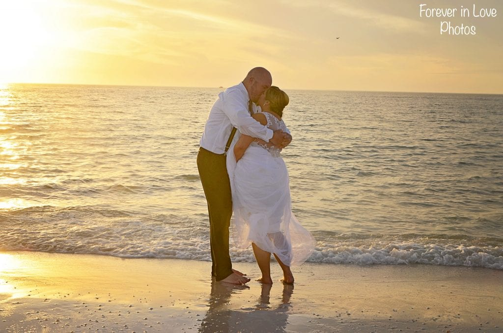 A bride and groom put their feet in the water during our sunset Clearwater Beach Weddings.