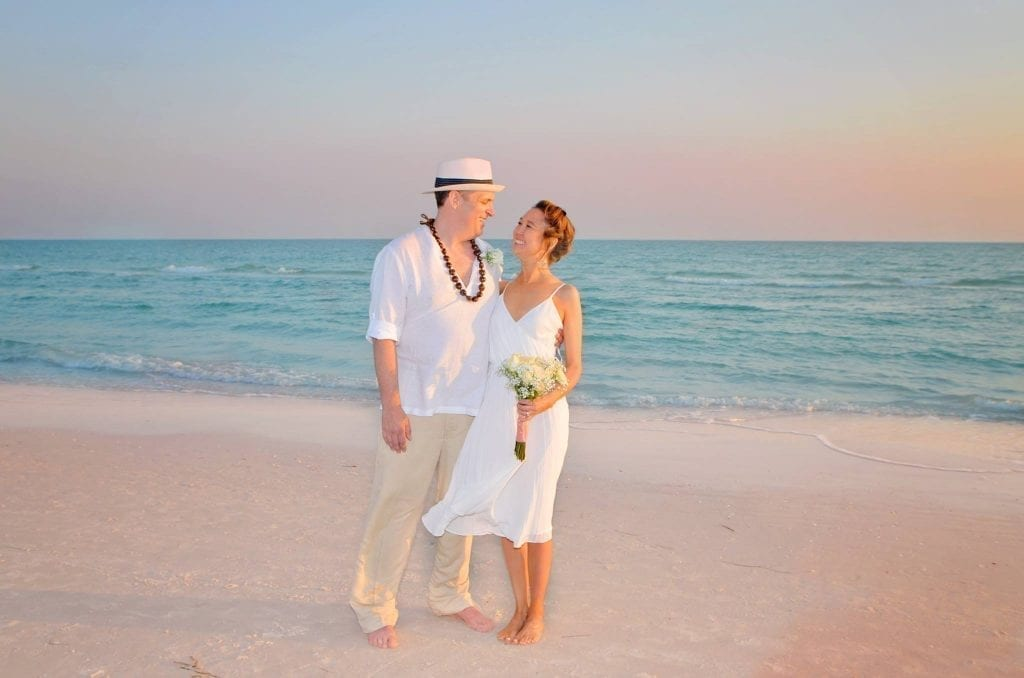Siesta Key Beach couple during the pink sunset at a Gulf beach wedding