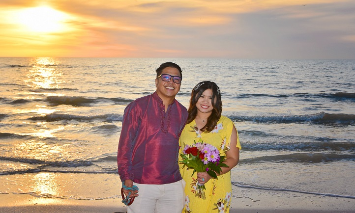 Bride and groom on Clearwater Beach as the sun sets over the water