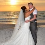 At a Beach Wedding in Clearwater, Florida the sun sets as the couple gaze into each others eyes.