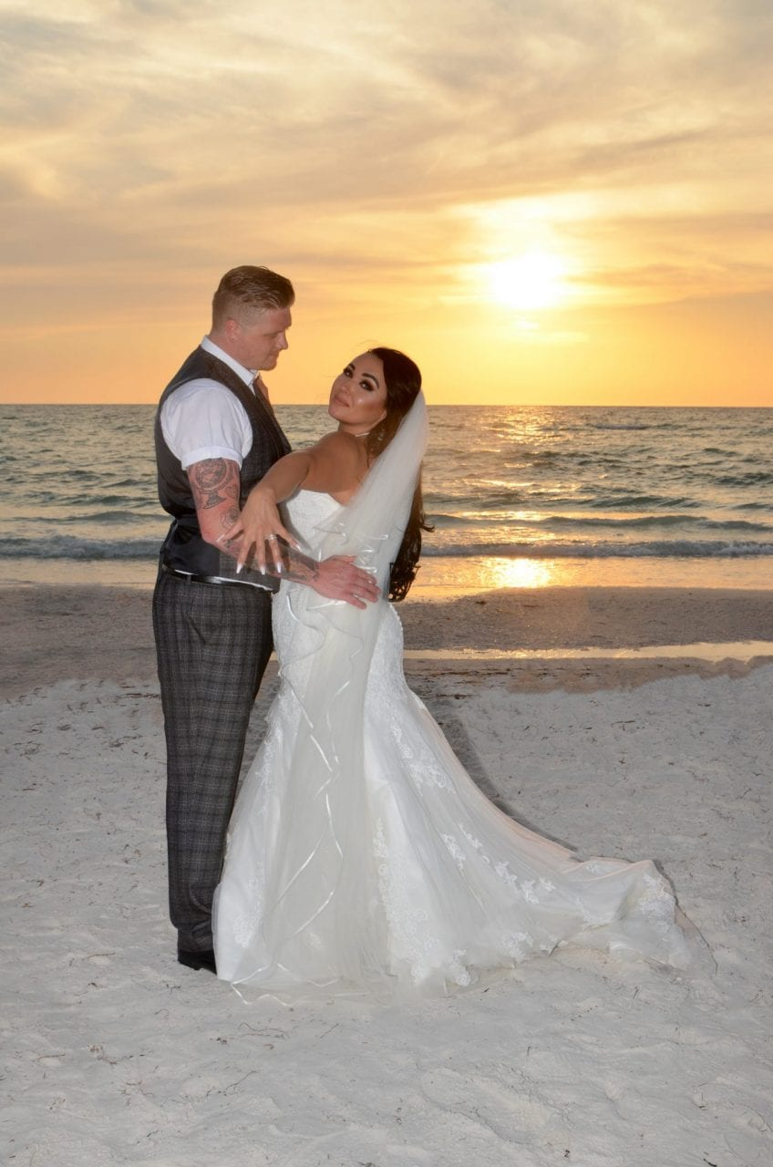 Couple exchanging wedding rings at sunset on the beach.
