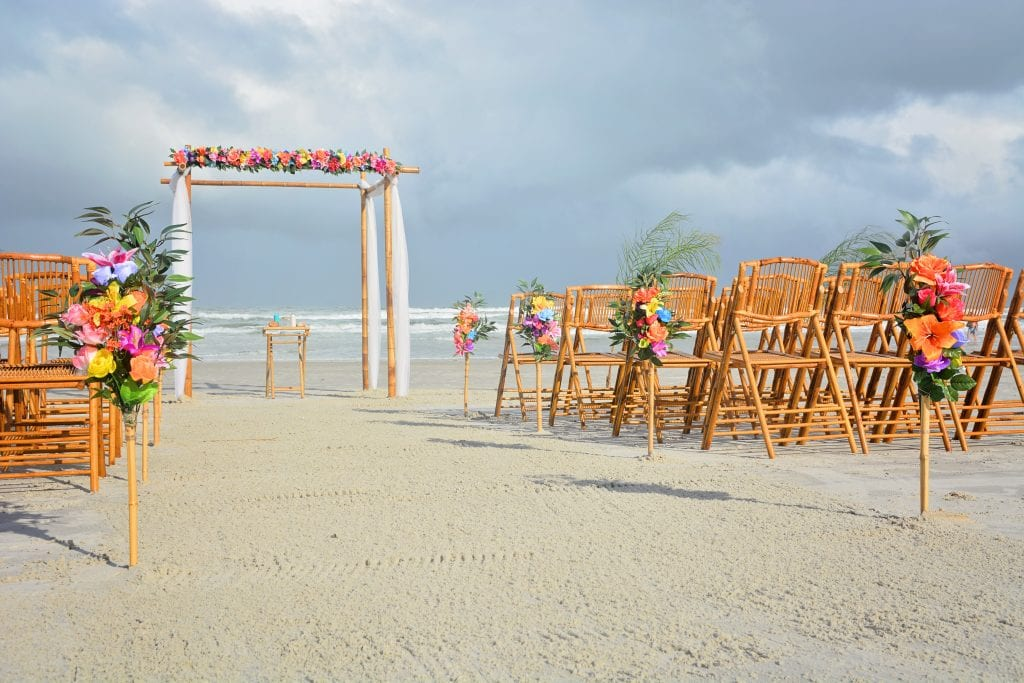 Destination Florida beach weddings with tropical beach decor and bamboo chairs in Daytona Beach.