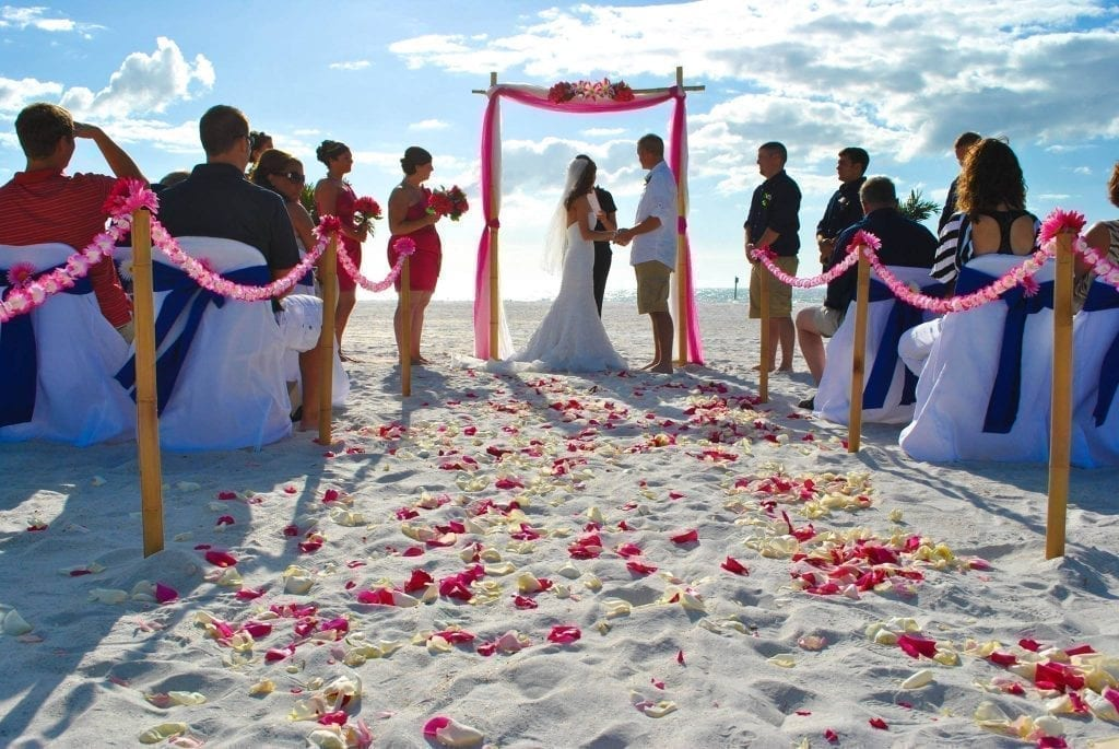 Beach Weddings in Florida with bamboo canopy, aisle way, fuschia and blue chair sashes.