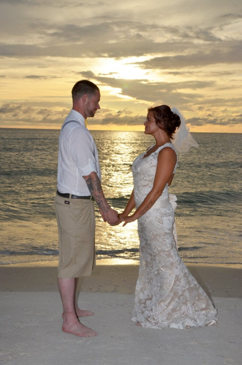 Couple holding hands at beach wedding St. Pete