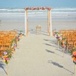 Destination beach weddings in Florida with bamboo chairs, bamboo canopy and tropical flowers.