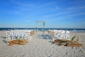 Driftwood beach wedding packages in Florida are alll-inlclusive with driftwood wedding accents, white chairs, driftwood beach wedding canopy and floral arrangements.