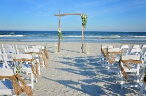 Driftwood beach wedding packages in Florida with asymmetrical floral arrangements, lanterns, chairs and burlap.