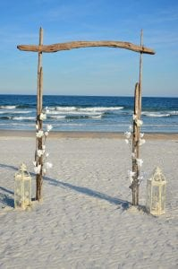 Driftwood beach wedding packages in Florida with floral and lantern accents
