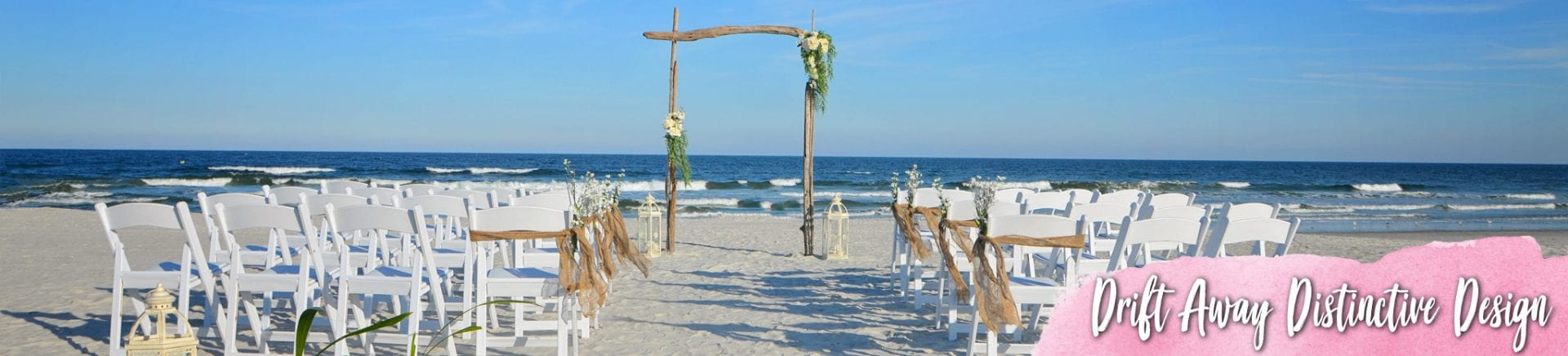 Driftwood wedding arch and white chairs with burlap sashes on the beach