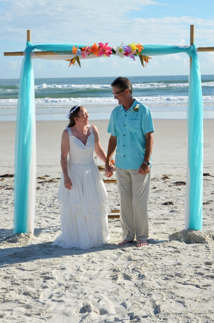 Just married couple under teal wedding arch at Florida beach wedding
