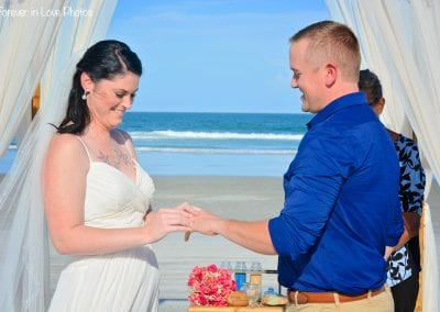 A bride puts a ring on her grooms hand during their Daytona Beach Elopement Ceremony.