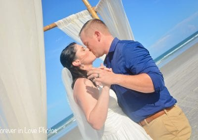 A bride and groom share a kiss under the bamboo canopy during their Daytona Beach Elopement Ceremony.