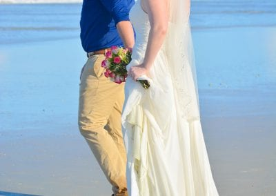 A groom walks his bride to the ocean during their Daytona Beach Elopement Ceremony.