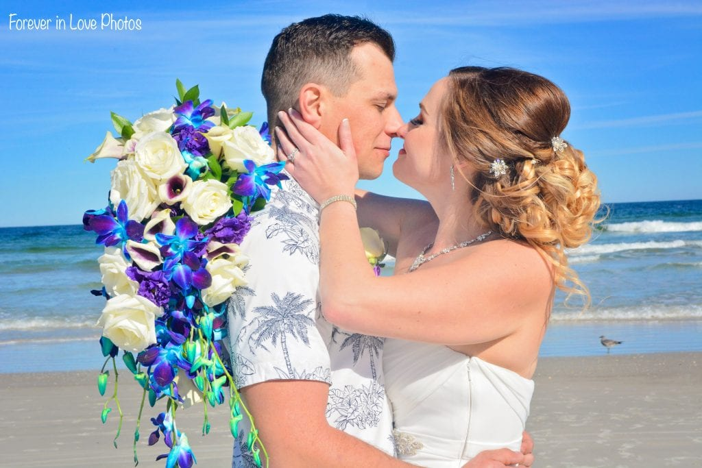Couple kissing at Daytona beach wedding with bridal bouquet