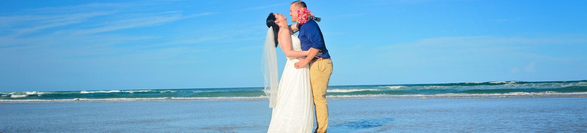 Couple kissing after beach wedding on sand