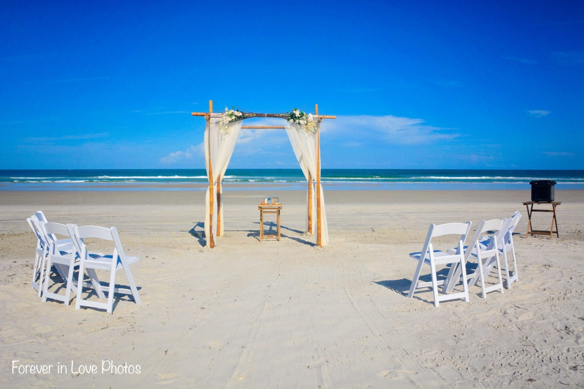 Simple bamboo wedding arch on Jacksonville beach with chairs
