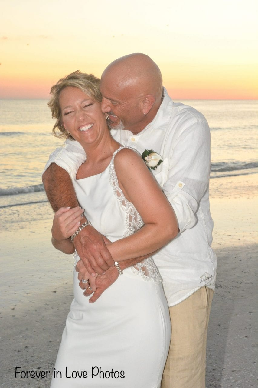 Couple hugging on the beach after sunset wedding in Florida