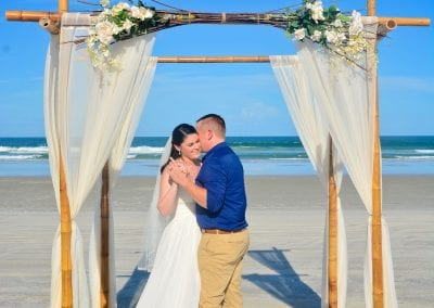 A bride and groom share a first dance under the bamboo canopy during their Daytona beach elopement ceremony.