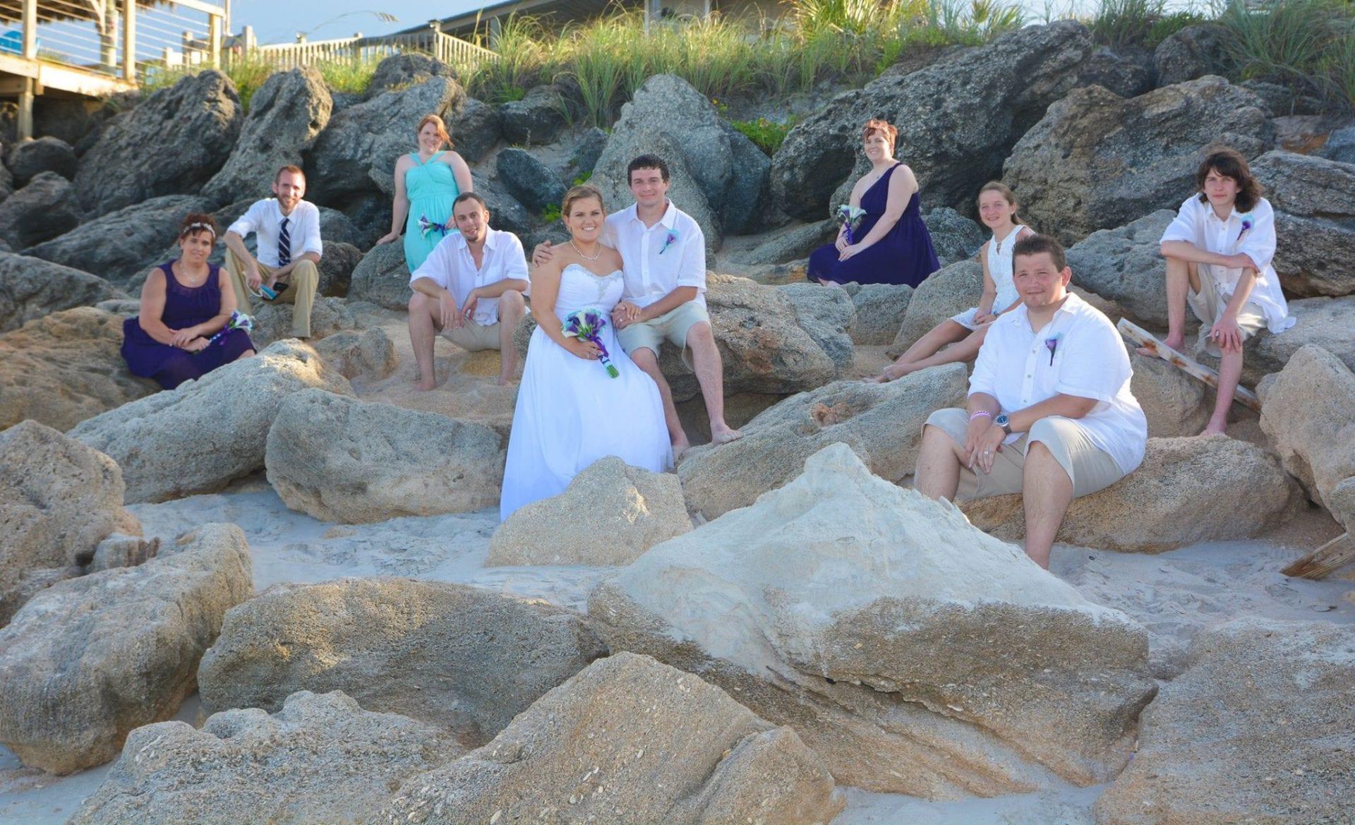 Bridal party on rocks after beach wedding on New Smyrna Beach, Florida