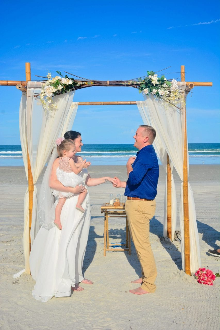 Couple saying vows on Daytona Beach with child