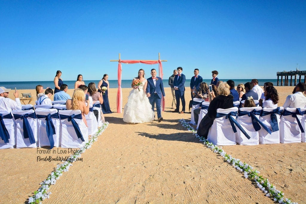 Couple walks down aisle after beach wedding setup on Daytona Beach, FL