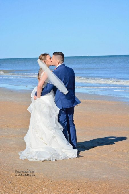 Wedding couple just married kissing on St. Augustine Beach