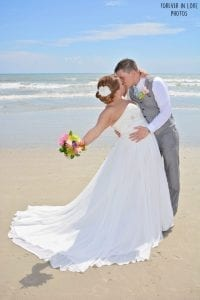 A groom dips his bride by the ocean at our Cocoa Beach Weddings in Florida.