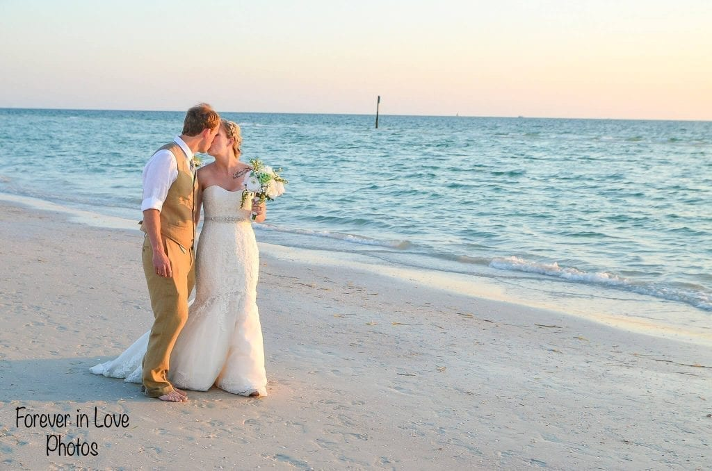 Couple strolls on beach with white sand after marriage in Madeira Beach, FL